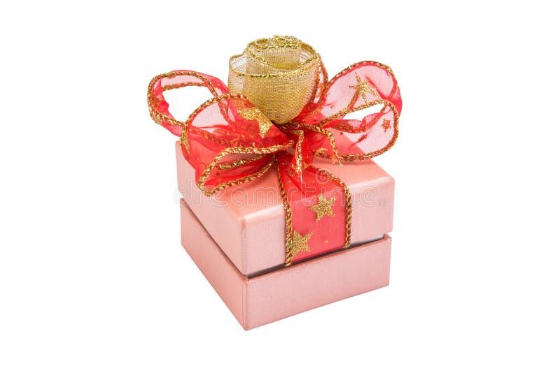 Roze giftdoos met gouden en rode die lintboog, op witte bedelaars wordt geïsoleerd stock foto
