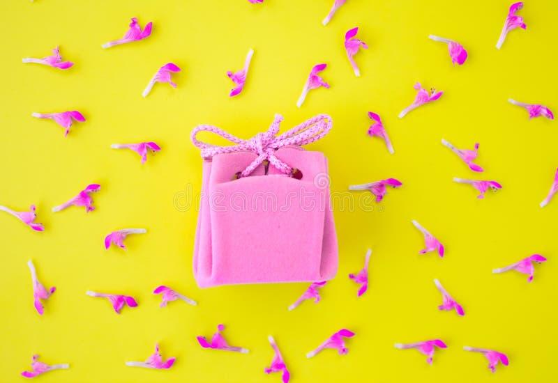 Roze giftdoos op een gele achtergrond met bloemen Feestelijk concept Vlak leg, hoogste mening royalty-vrije stock foto