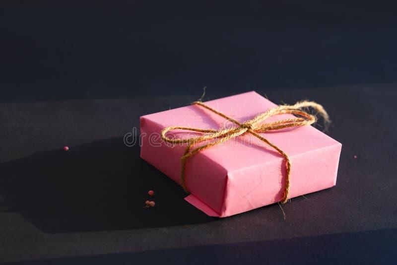 Roze giftdoos op een zwarte achtergrond Minimaal concept stock afbeelding