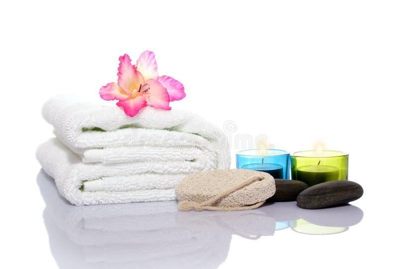 Roze gladiola, handdoek, kaarsen en rivierstenen royalty-vrije stock foto's