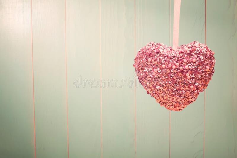 Roze glanzend hart op uitstekende groene houten achtergrond stock foto