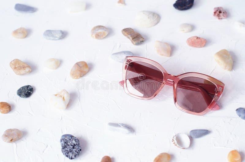 Roze glazen op een weefsel witte achtergrond met overzeese kiezelstenen stock fotografie