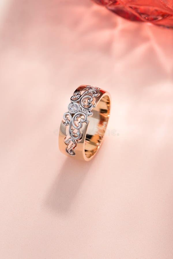 Roze goud en witgoudornamentring met diamant op pastelkleurachtergrond royalty-vrije stock afbeeldingen