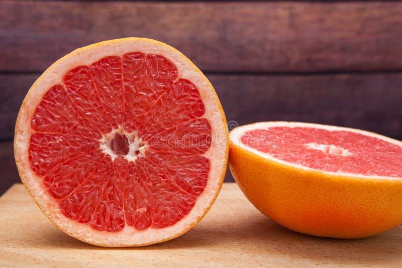 Roze grapefruit of pompelmoes op houten achtergrond - tropische citrusvruchten stock foto
