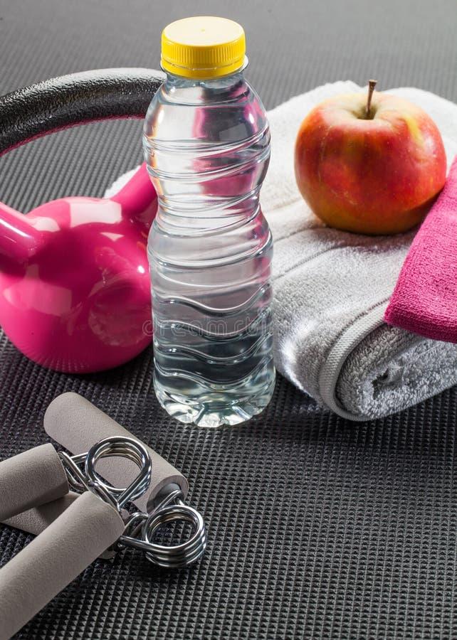 Roze gymnastiek en dieettoebehoren met kettlebell en handgreep stock foto's