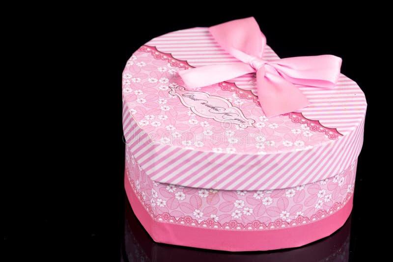 Roze hart gevormde doos boven zwarte achtergrond met bezinningen royalty-vrije stock afbeeldingen