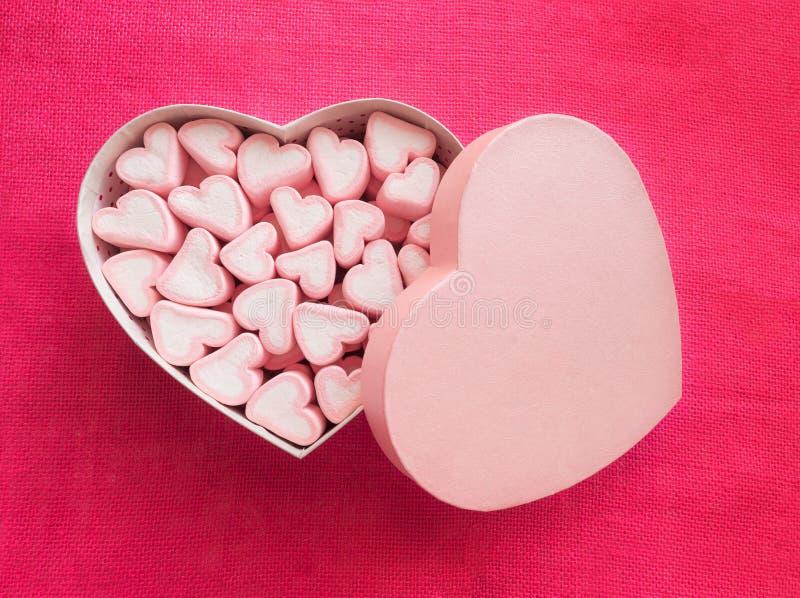 Roze heemst in een giftdoos in vorm van hart op textielachtergrond, Vele hartenheemst voor heden, Snoepjes binnen stock foto's