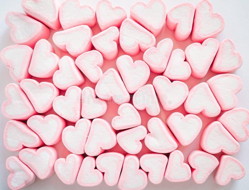 Roze heemstachtergrond, Vele hartenheemst, Snoepjes in de vorm van harten van heemst De daggift van Valentine ` s stock foto