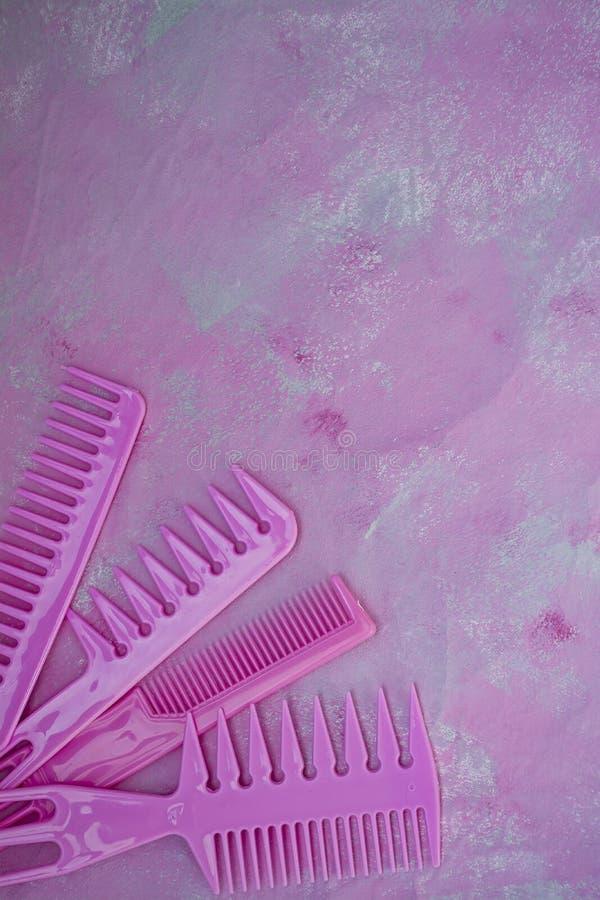 Roze heldere kam voor kappers Schoonheidszaal Hulpmiddelen voor kapsels Roze achtergrond barbershop Reeks verschillende haarborst royalty-vrije stock afbeelding