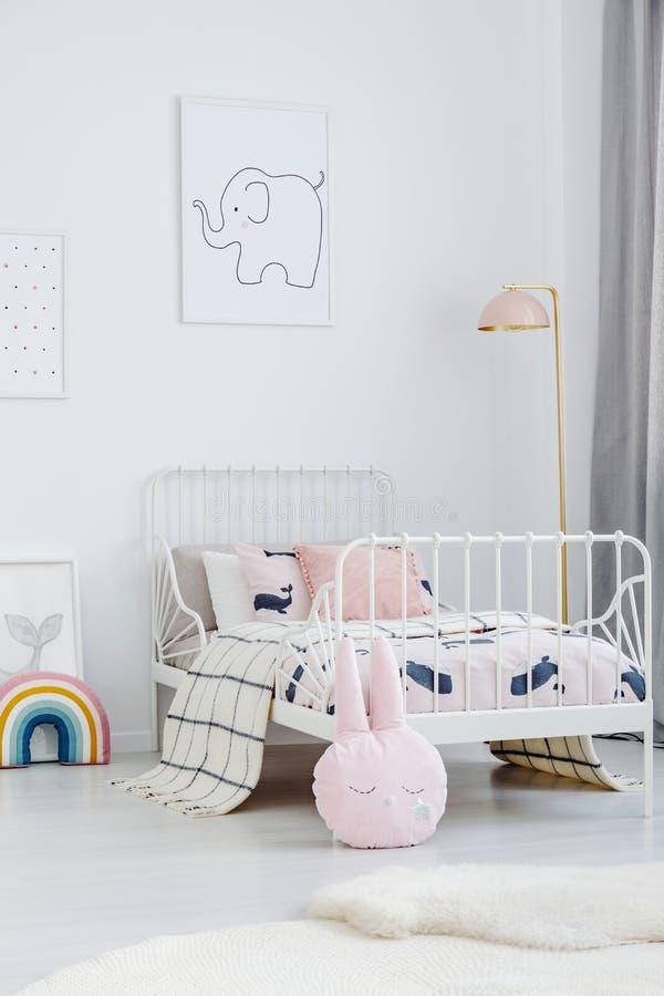 Roze hoofdkussen naast wit bed in het binnenland van de meisjes` s slaapkamer met La royalty-vrije stock foto
