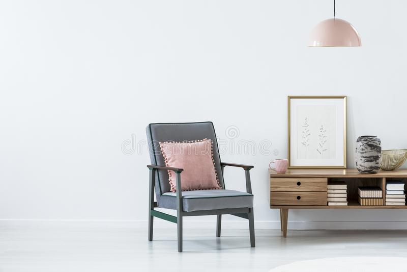 Roze hoofdkussen op blauwe leunstoel naast een houten kast in het leven royalty-vrije stock foto