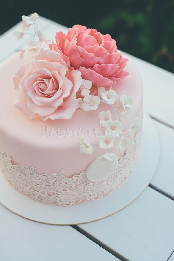 Roze huwelijkscake met dicht omhoog het berijpen en suikerrozen royalty-vrije stock fotografie