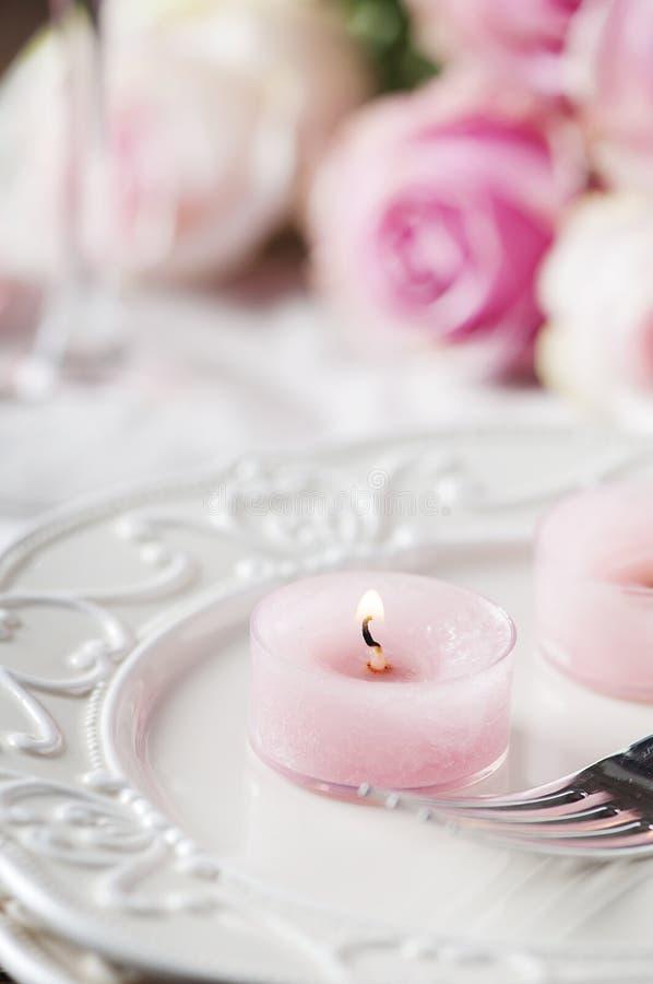 Roze kaars en rozen op de lijst stock fotografie