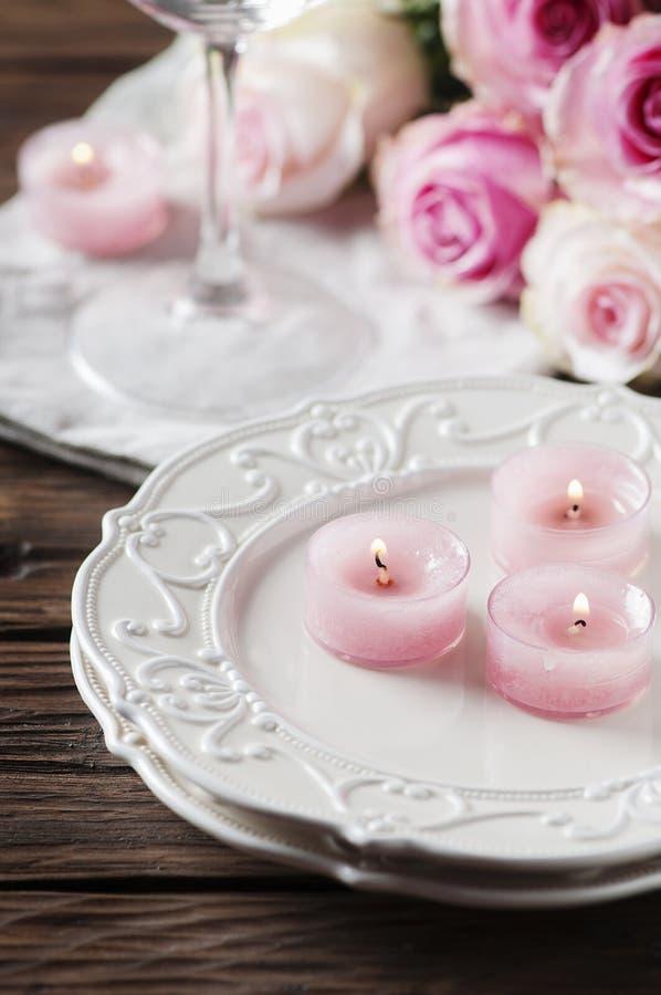 Roze kaars en rozen op de lijst royalty-vrije stock foto