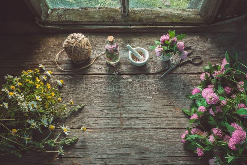 Roze klaver, madeliefjes en hypericumbloemen, mortier, klavertint of infusie, schaar en jute stock afbeelding