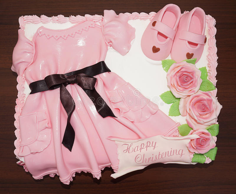 Roze kledingscake met schoenen en bloemen voor doopsel en doopsel stock foto's