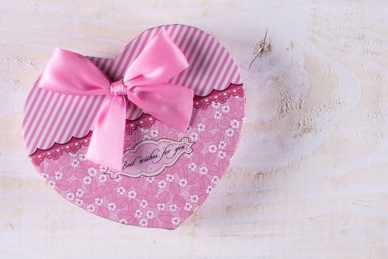Roze kleurenhart gevormde doos met roze boog boven houten achtergrond stock fotografie