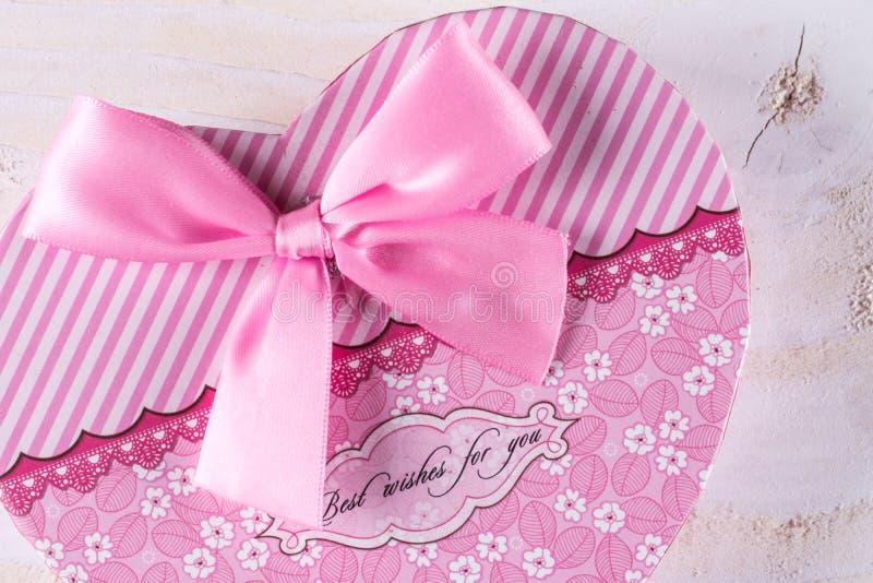 Roze kleurenhart gevormde doos met roze boog boven houten achtergrond royalty-vrije stock fotografie