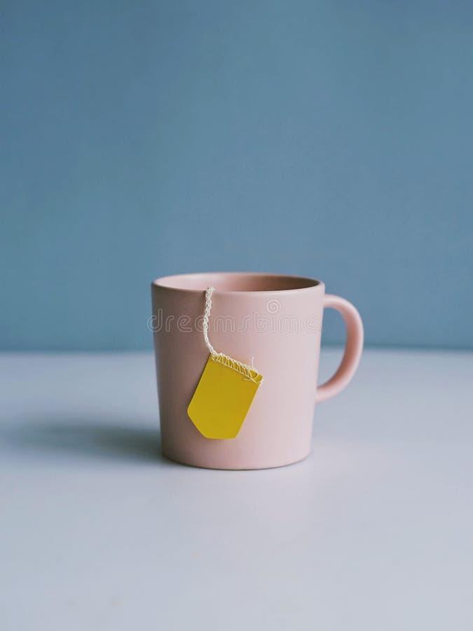 Roze kop thee op een lichtblauwe achtergrond stock foto