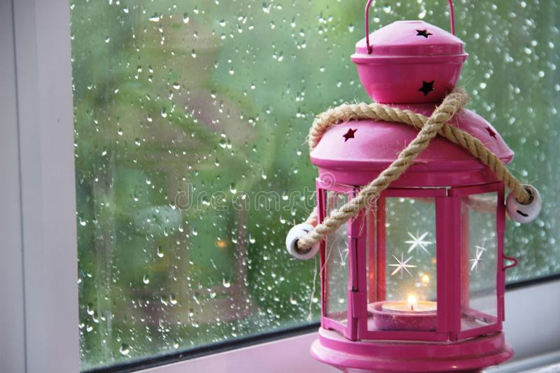 roze lantaarn met een brandende kaars op het venster op een regenachtige de zomerdag, selectieve nadruk, close-up, ruimte voor te stock afbeeldingen