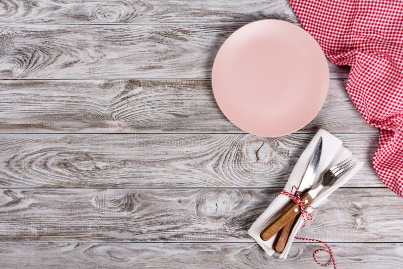 Roze lege plaat en vork en mes op houten textuurachtergrond Romantisch dinerconcept stock afbeeldingen