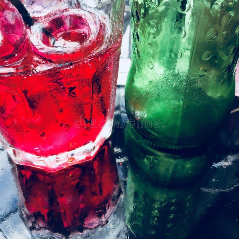 Roze limonade en zijn fles op een glaslijst stock foto