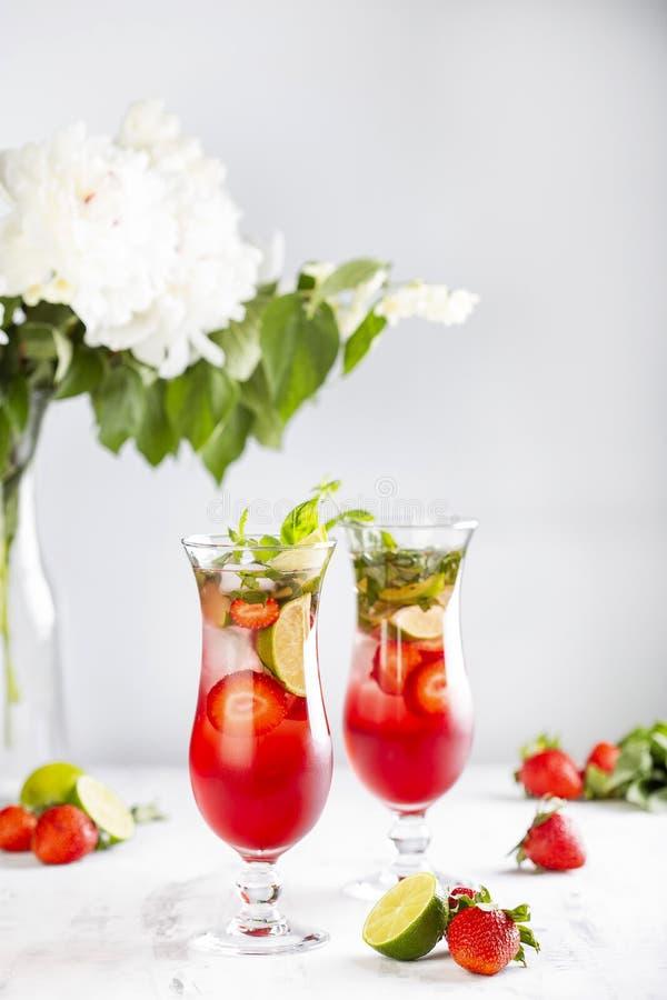 Roze limonade met aardbeien, kalk, basilicum en munt royalty-vrije stock foto