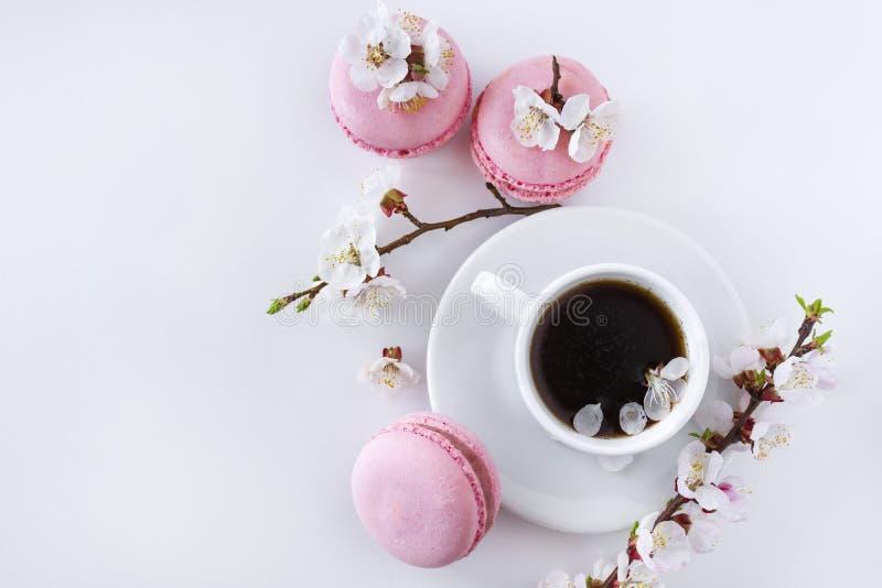 Roze makarons met een kop van koffie en een tak van witte bloemen stock afbeelding