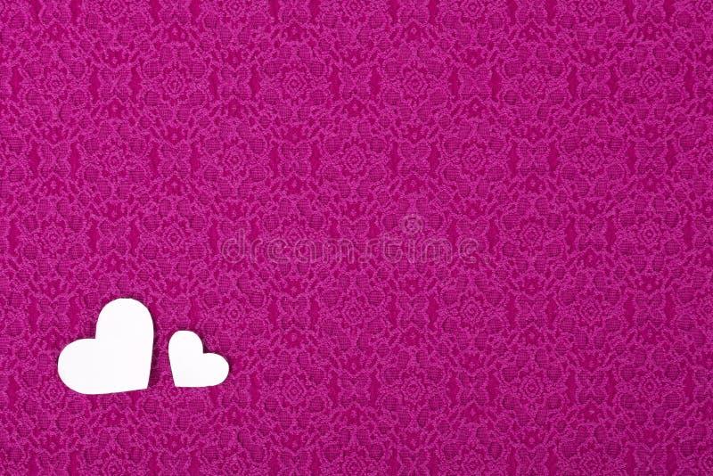 Roze materiaal met twee harten, een achtergrond, Valentijnskaartendag. stock fotografie