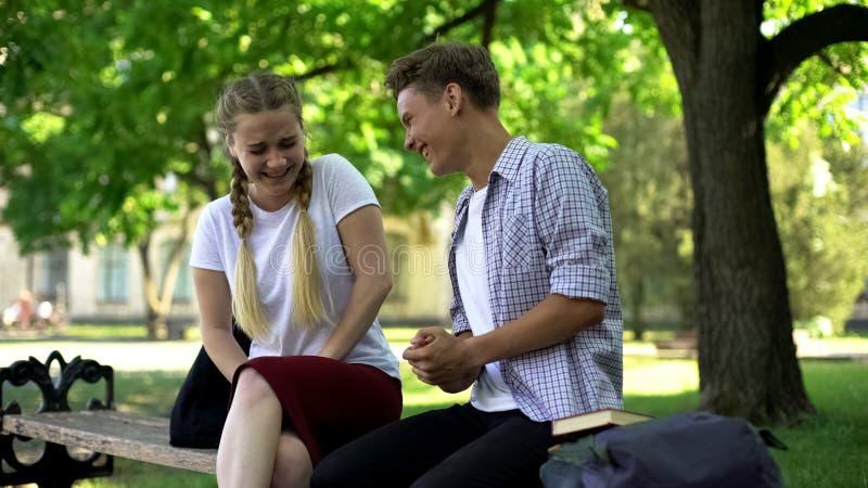 Roze?miani przyjaciele siedzi na ?awce w parku, m?wi niezwykle ?mieszn? opowie??, dowcip zdjęcia stock