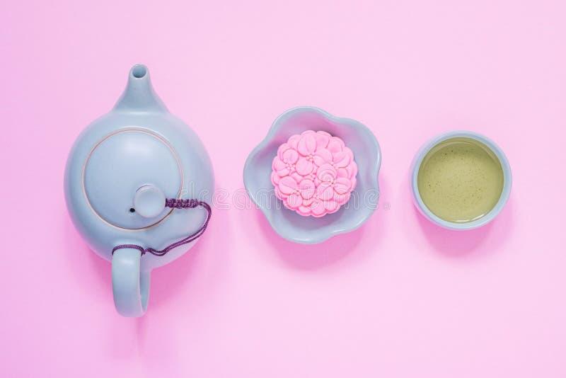 Roze mooncake, blauwe theepot, kop van groene thee op een roze achtergrond Het Chinese voedsel van het de medio-herfstfestival stock foto