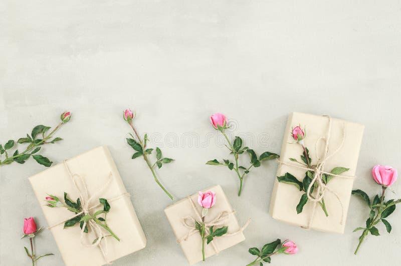 Roze nam bloemen, giftvakje of heden op grijze steenlijst toe stock foto