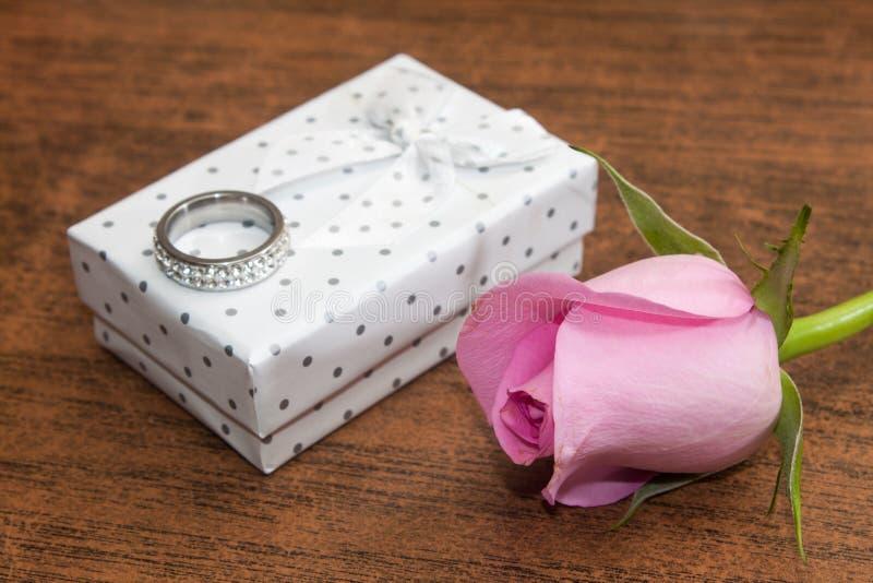 Roze nam en doos met verlovingsring op de houten achtergrond toe stock fotografie