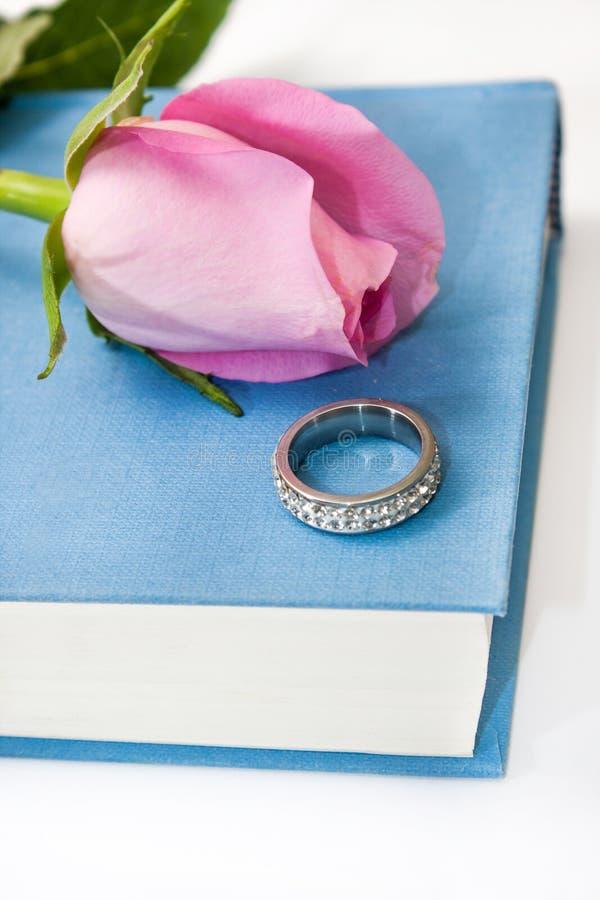 Roze nam en ring op het boek toe stock foto