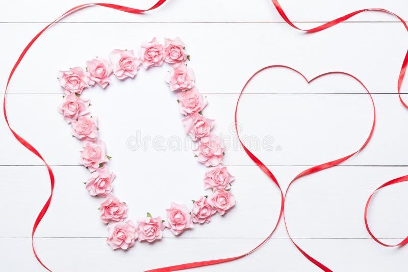 Roze nam kader met hart gevormd rood lint over witte houten B toe royalty-vrije stock foto's