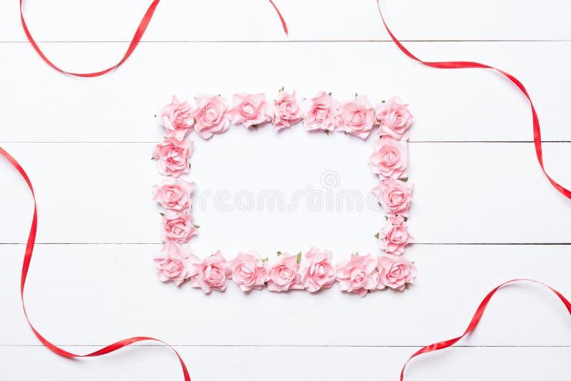 Roze nam kader met rood lint over witte houten achtergrond toe royalty-vrije stock fotografie