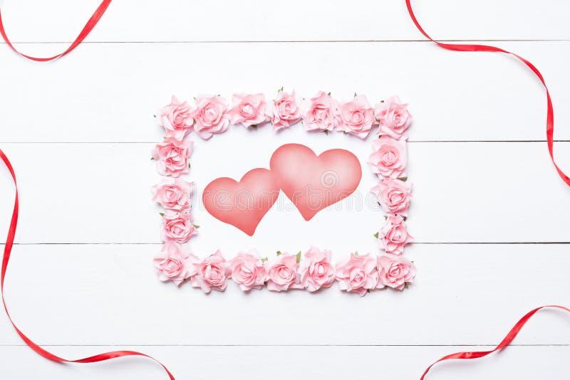 Roze nam kader met twee harten over witte houten lijst toe royalty-vrije stock afbeeldingen