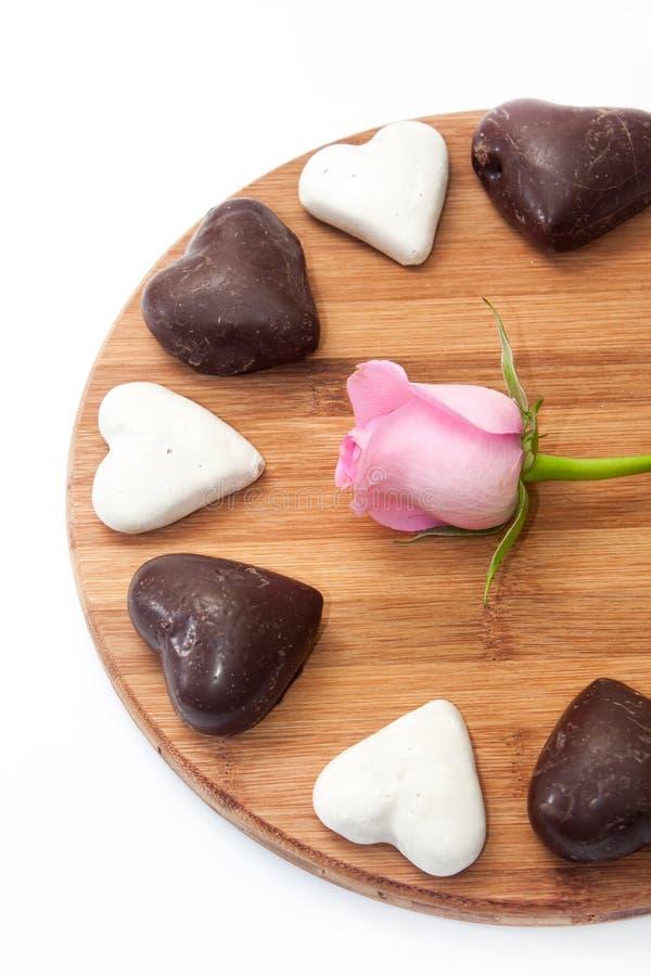 Roze nam met zwart-witte hartkoekjes toe op de houten raad stock foto's