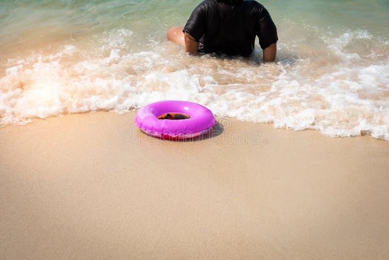 Roze opblaasbare rubberring op het strand in ondiep water royalty-vrije stock afbeeldingen