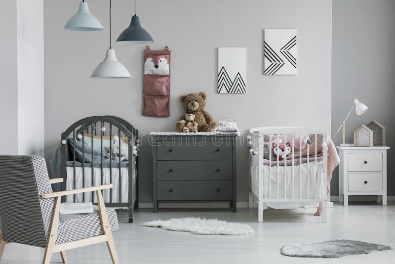 Roze organisator op muur van in babyslaapkamer met twee voederbakken en ladenkast stock afbeeldingen