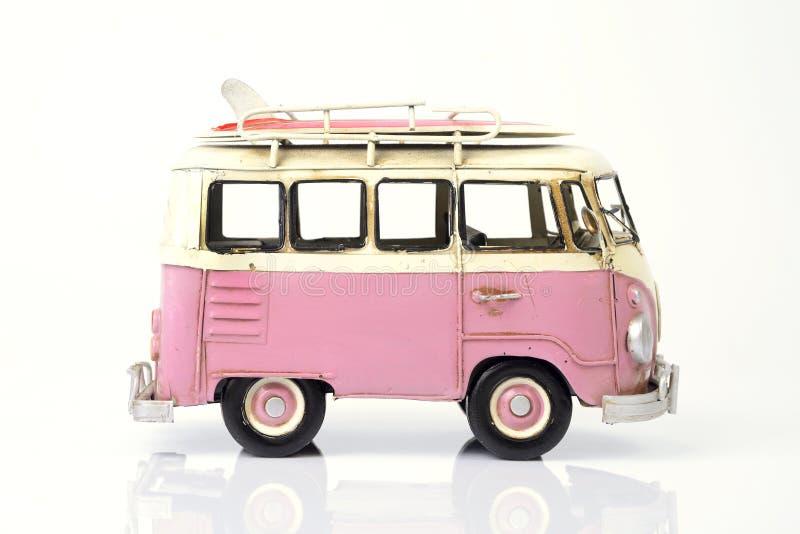 Roze oude stuk speelgoed auto met surfplank stock foto