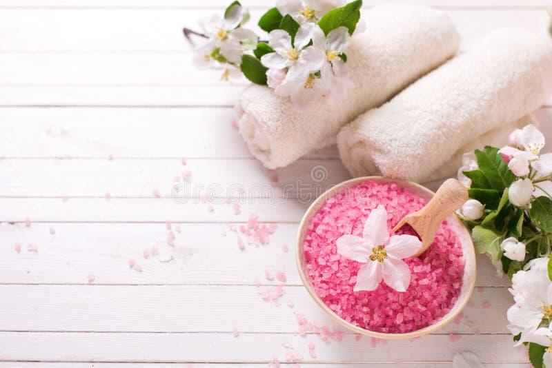 Roze overzees zout in kom, handdoeken en bloemen op witte houten backg royalty-vrije stock afbeeldingen