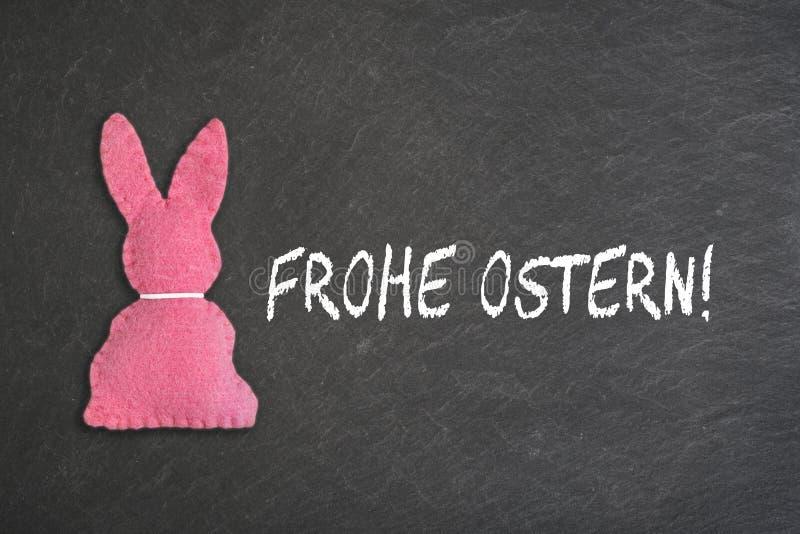 Roze Paashaas met tekst 'Frohe Ostern 'op een bordachtergrond Transla stock afbeeldingen