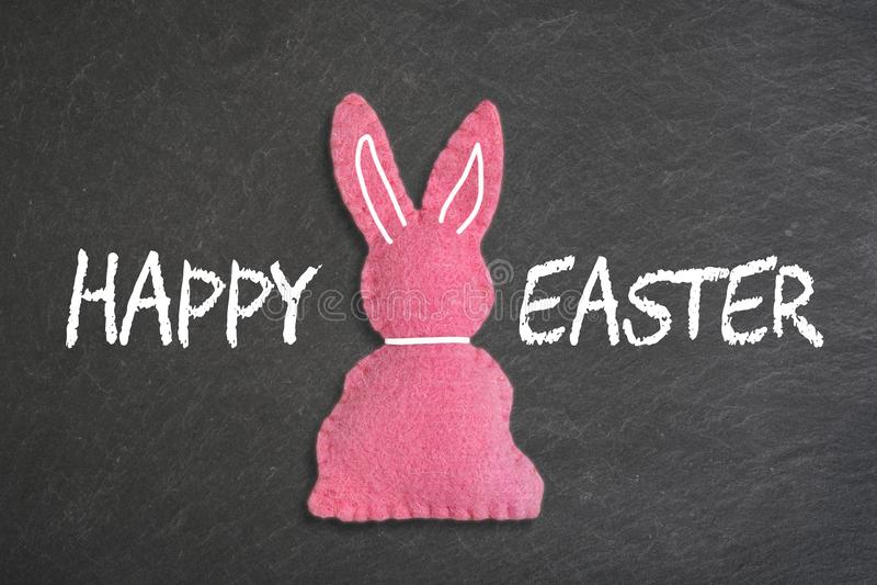 Roze Paashaas met tekst 'gelukkige Pasen 'op een bordachtergrond royalty-vrije stock foto
