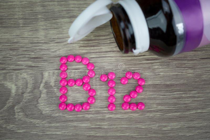 Roze pillen die vorm vormen aan B12 alfabet op houten achtergrond stock foto's