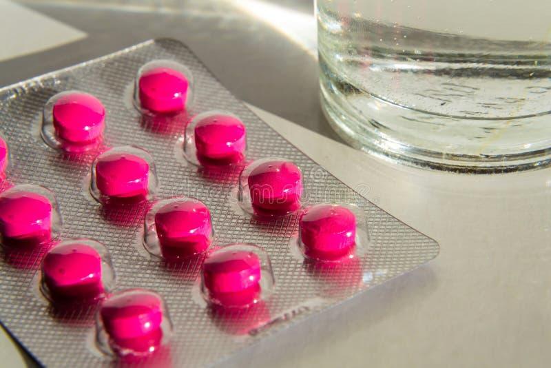Roze pillen met glas water op witte achtergrond stock foto's