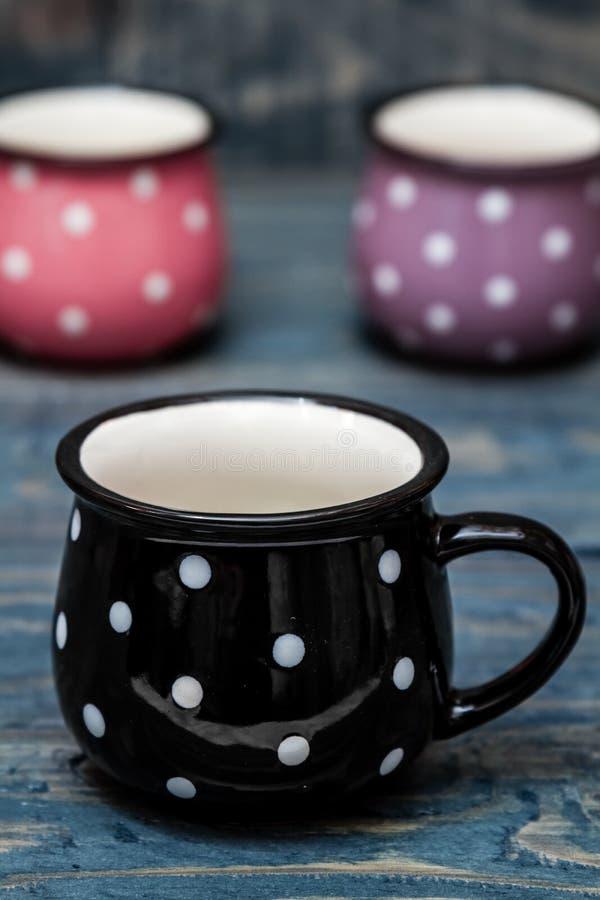 Roze, Purpere en Zwarte Ceramische Mokken met Witte Punten op Blauw Hout royalty-vrije stock afbeelding