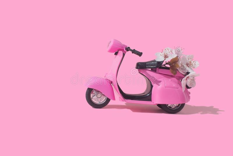 Roze retro stuk speelgoed fiets die boeket van bloemendoos leveren op roze achtergrond 14 februari kaart, de dag van Valentine De royalty-vrije stock foto