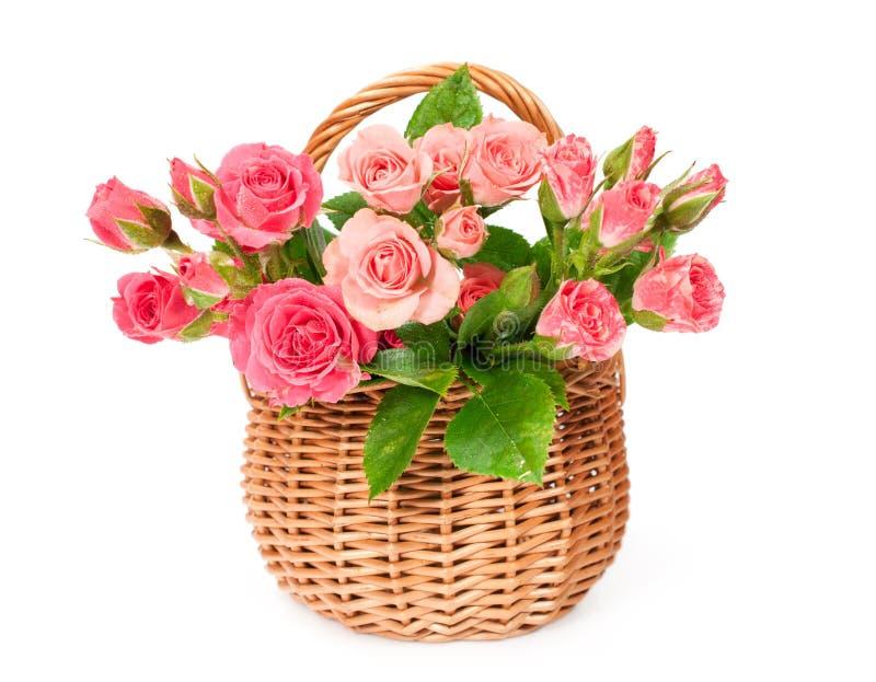 Roze rozen in een rieten mand stock afbeelding