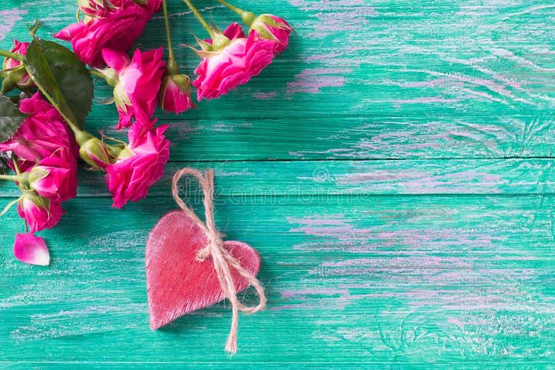 Roze rozen en rood houten hart stock afbeelding